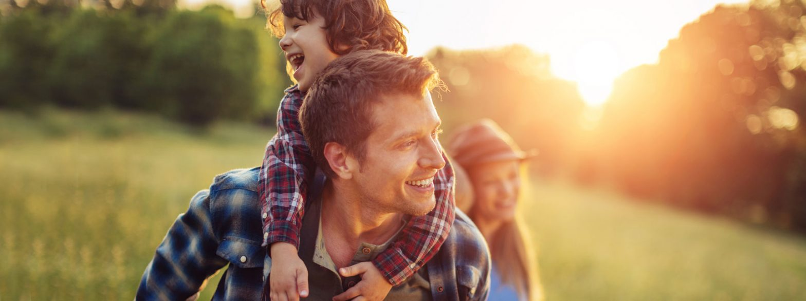 smiling laughing dad kid piggyback mom in background outside sunset field meadow plaid shirt vitamin D foods and supplement benefits vitafusion experience blog